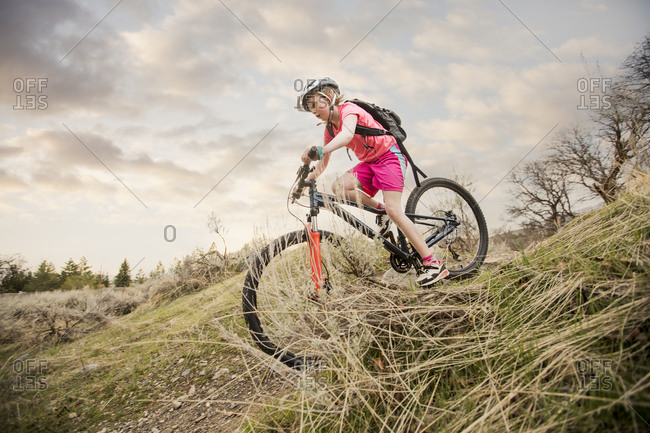 Caucasian girl riding bicycle on hill