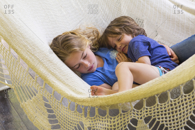 Caucasian brother and sister cuddling in hammock