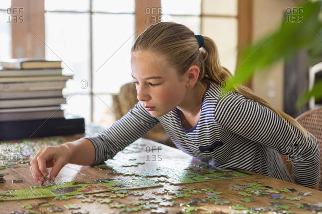 Caucasian girl solving jigsaw puzzle