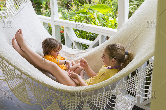 Caucasian brother and sister laying in hammock eating snack