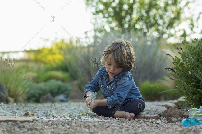 Caucasian boy sitting on ground smashing rocks with hammer