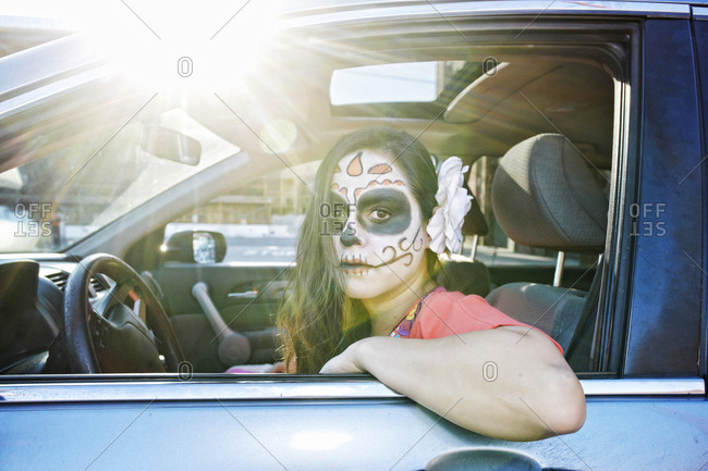 Hispanic woman driving car wearing skull face paint