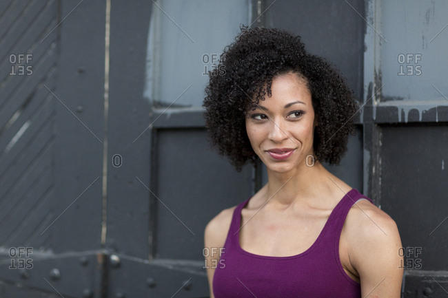 Smiling Mixed Race woman leaning on door