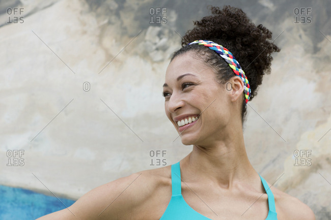 Portrait of smiling Mixed Race woman near wall