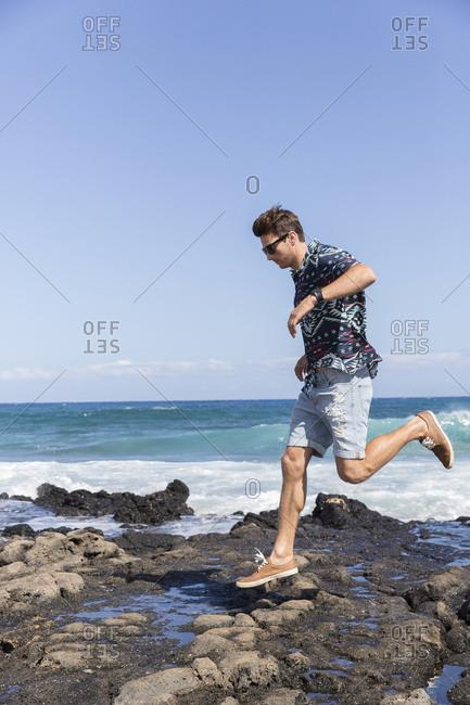 Caucasian man running on rocks on beach