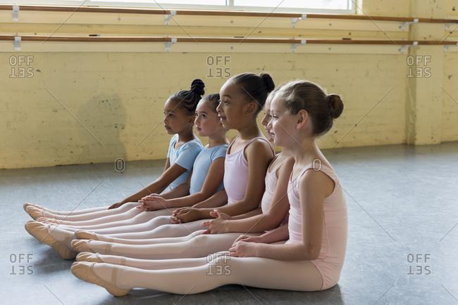 Girls sitting in a row on floor of ballet studio