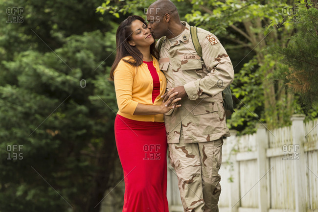 African American soldier kissing wife on cheek