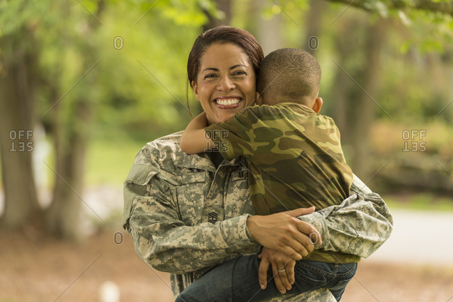 African American soldier mother carrying and hugging son
