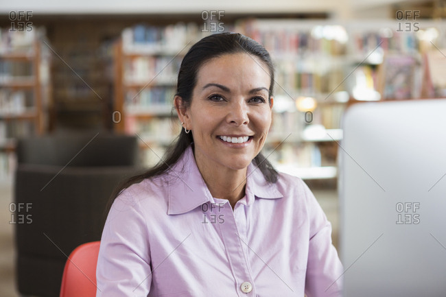 Smiling Hispanic woman using computer in library