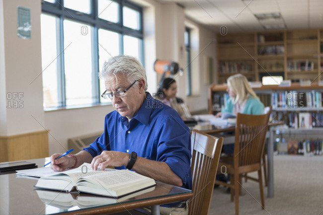 Older man reading book in library and writing notes