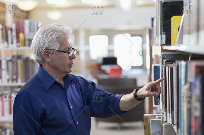 Curious Hispanic man searching for book in library