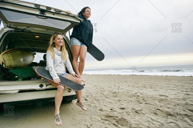 Caucasian women in car hatch at beach holding skateboards