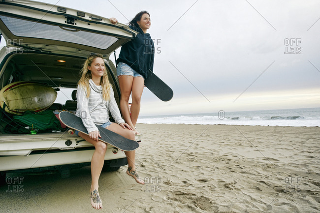 Caucasian women in car hatch at beach holding skateboards