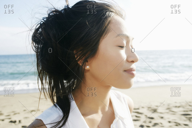 Portrait of Vietnamese woman at beach with eyes closed