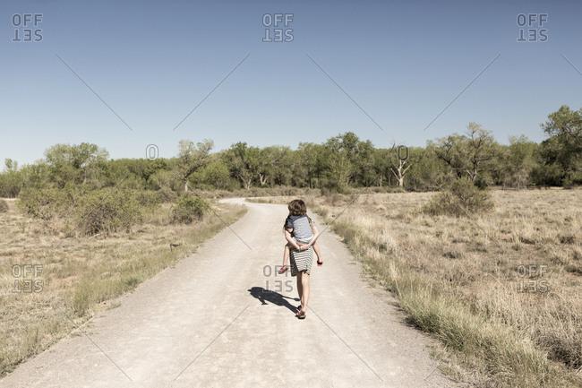 Caucasian girl carrying brother piggyback on dirt path