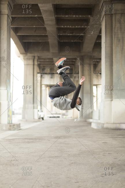 Mixed Race man jumping upside-down under bridge