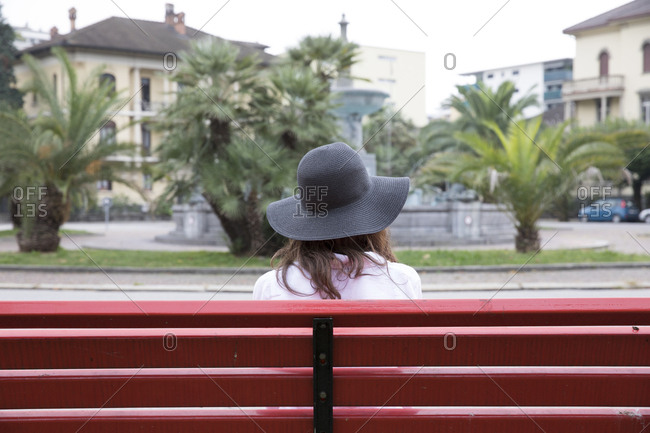 Woman wearing sun hat sitting on red bench