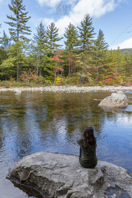 Caucasian woman sitting on rock relaxing near river