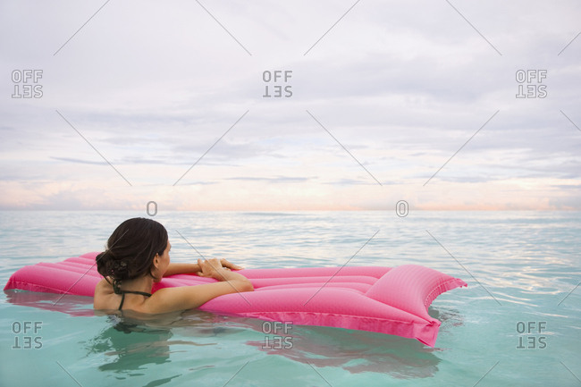 Mixed Race woman floating in ocean on inflatable raft