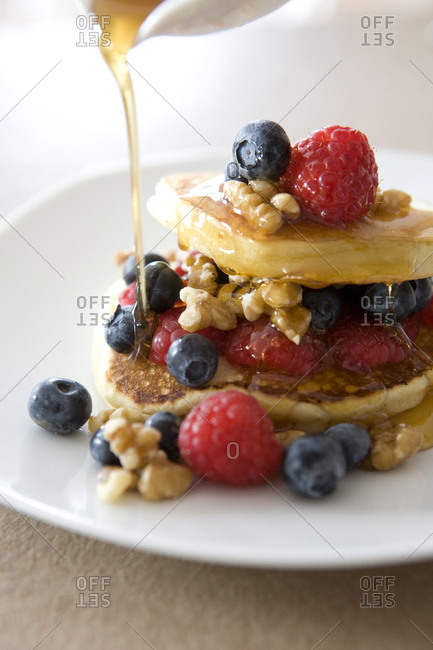 Syrup pouring on pancakes with fruit and nuts