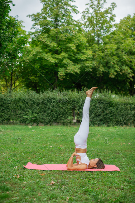 Woman in shoulder stand on yoga mat in park