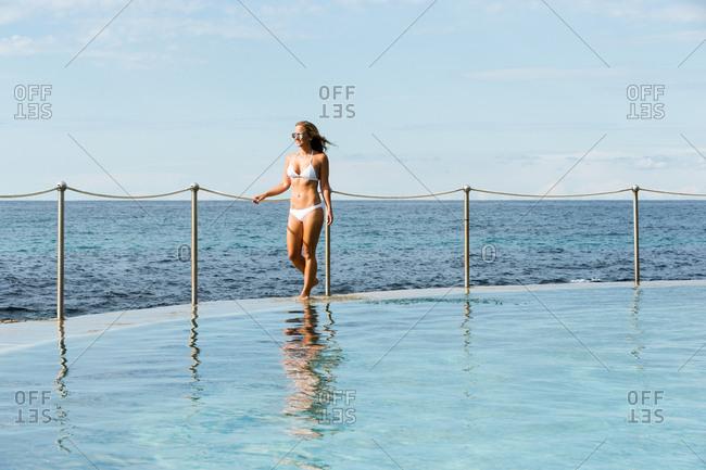 Woman in white bikini walking along edge of waterfront pool