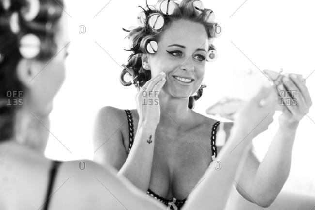 Woman with her hair set in rollers putting on makeup