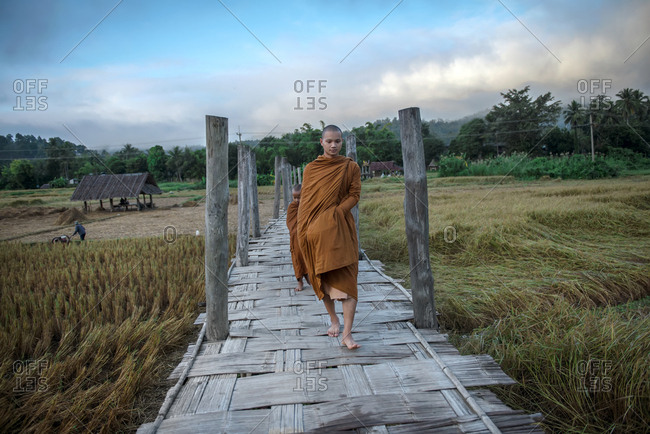 Mae Hong Son, Thailand - November 12, 2014: Monks going on alms round crossing bamboo bridge in Mae Hong Son, Thailand-2014