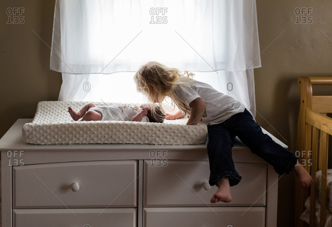 A sister kisses newborn baby on changing table