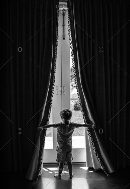 Boy opening window curtains