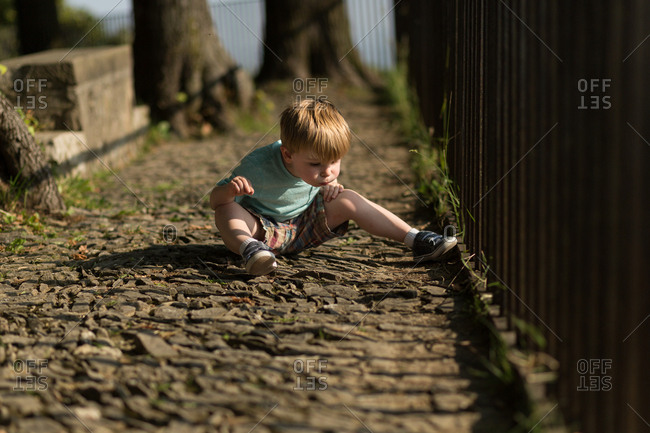 Boy blowing away dirt on cobblestones