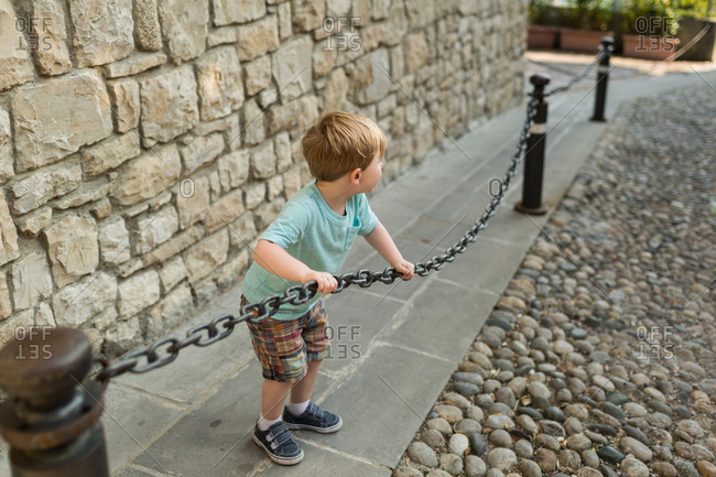 Boy playing with chain fence