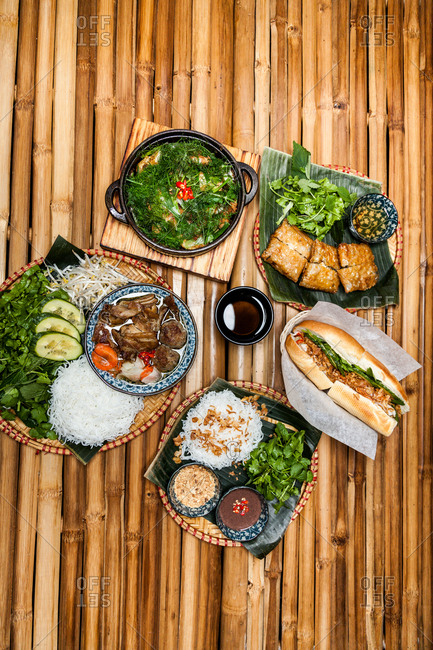 Variety of Vietnamese dishes on a bamboo table