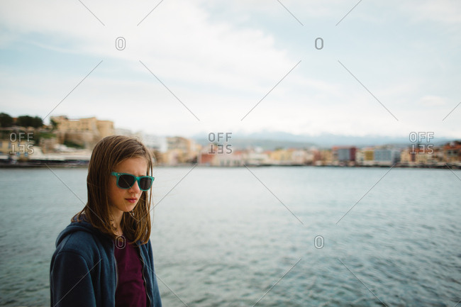 Young girl wearing sunglasses standing on shore of Chania, Crete, Greece