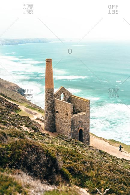 Walking by abandoned coastal stone tower