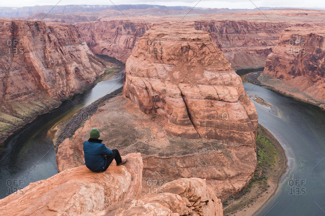 Person sitting on cliff overlooking Horseshoe Bend, Page, Arizona