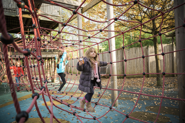 Children climbing through playground rope structure