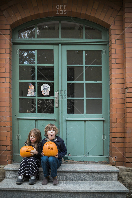 Brother and sister sitting on front step holding carved jack-o'-lanterns