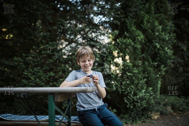 Smiling boy sitting at picnic table looking at magnifying glass