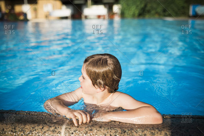Boy hanging on the edge of a swimming pool