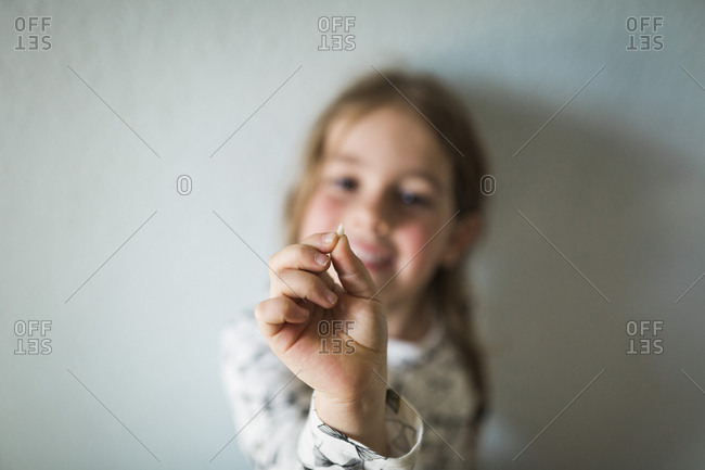 Girl holding her tooth