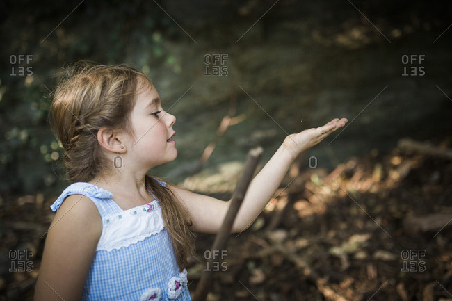 Girl holding a stick playing in the forest