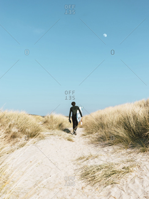 Surfer walking through sand dunes
