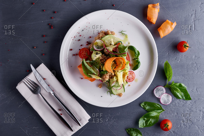 Directly above view of a plate with appetizing vegetable salad with quinoa served on gray table with cutlery