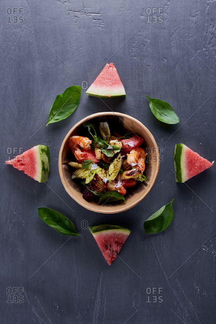 Directly above view of bowl with tasty seafood salad beautifully served on table with slices of watermelon