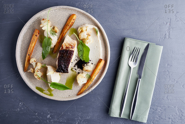 Directly above view of delicious dish with cod, roasted carrots, cauliflower and mashed potato served on table with cutlery