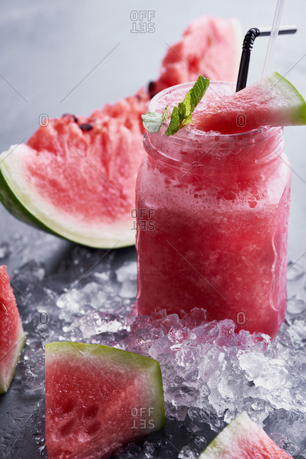 A glass jar of refreshing watermelon smoothie beautifully served with mint, ice and ripe watermelon slices