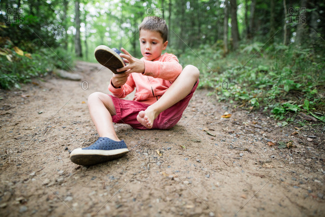 Boy taking off shoe on forest trail