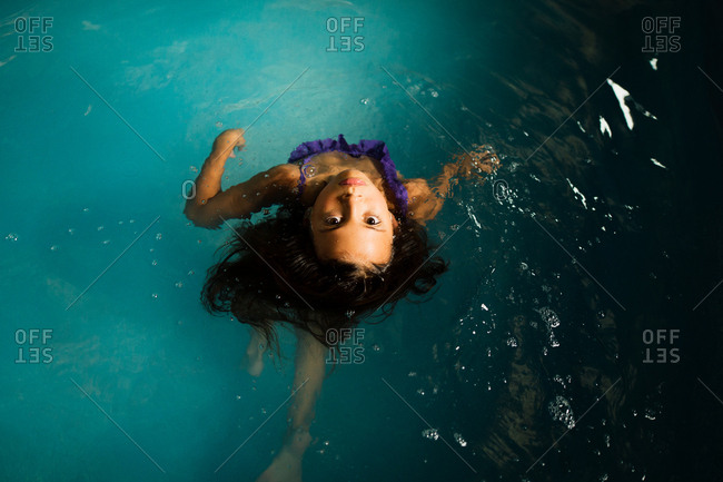 Girl looking up from a pool