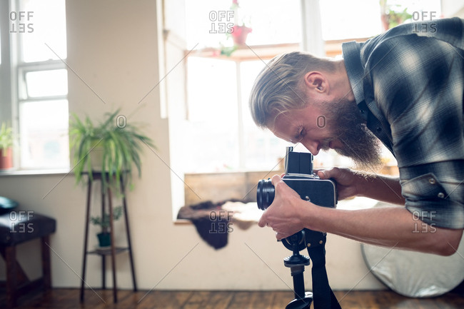 Side view of male photographer photographing through camera in studio